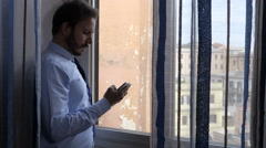 Attractive business man at the window use the phone Stock Footage
