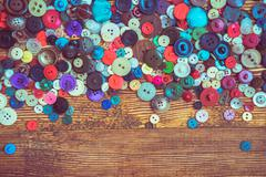 Clothes buttons on wooden baclground Stock Photos