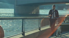 4K Hipster businessman with bicycle walking through city & looking at smartphone Stock Footage