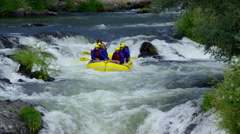 Group of people white water rafting off waterfall Stock Footage