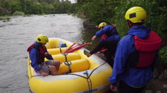 Group of people white water rafting getting into raft Stock Footage