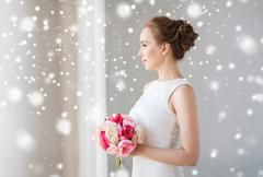 Bride or woman in white dress with flower bunch Kuvituskuvat