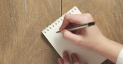 Female teen writes things to do on blank notepad Stock Footage
