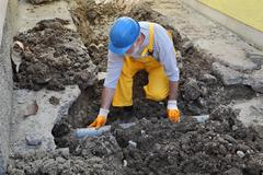 Plumber at construction site repair sewerage tube Stock Photos