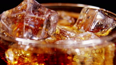 Cola background. Pouring Cola with Ice and bubbles Stock Footage