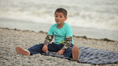 Boy sitting on the beach Stock Footage