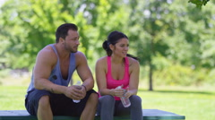 Couple at park take a water break Stock Footage