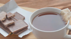 Putting sugar and tea bag in a glass mug with hot water Stock Footage