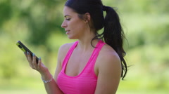 Athletic woman at park talks on cell phone Stock Footage
