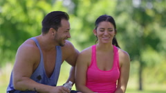 Athletic couple at park take a water break Stock Footage