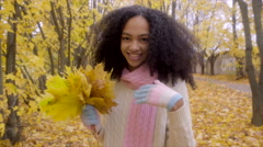 Cute teen girl running across autumn forest Stock Footage