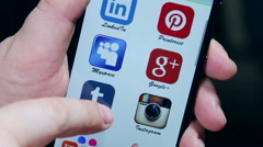 Popular social media logo scroll your finger on a smartphone Stock Footage