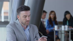 Young businessman using cell phone in office lobby Stock Footage
