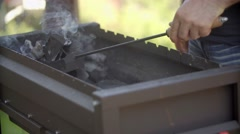 The man mixes coals in a brazier. the man stirs coals. the man mixes coals in a Stock Footage
