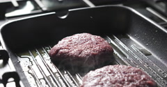 Beef patty on grill pan Stock Footage