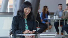 Mature Asian businesswoman using cell phone in office lobby Stock Footage