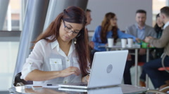Hispanic businesswoman using laptop computer in office lobby Arkistovideo