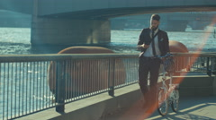 4K London businessman with bicycle texting on phone as he walks through city. Stock Footage