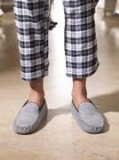 Male feet wearing grey bedroom slippers Stock Photos