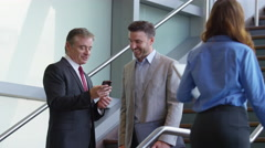 Two businessmen meeting on stairs of office lobby looking at cell phone Stock Footage