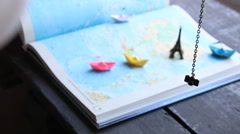 Vacation planner idea. Tourism. Paper boats on the map and the Eiffel Tower Stock Footage