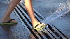 Children's feet in flip flops in a spray of water from a fountain Stock Footage