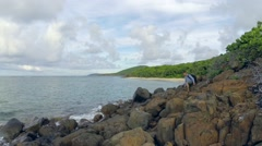 Man hiking rocky tropical shoreline Stock Footage