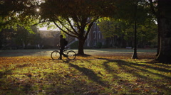 College student on campus walking with bicycle Stock Footage