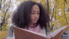 Close up of cute black teen girl with drawing album in autumn forest Stock Footage