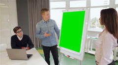 Man and woman show something on flipchart Stock Footage