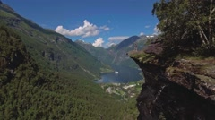 Woman hiker enjoying scenic landscapes at a cliff edge, Geirangerfjord, Norway Stock Footage