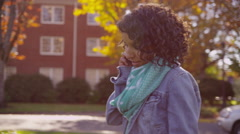 College student on campus in fall talking on cell phone Stock Footage