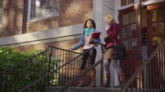 Two college students on campus walking down stairs Stock Footage