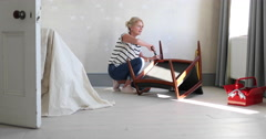 Mature female repairing an old chair Stock Footage