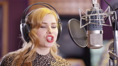 4K Portrait smiling female vocalist in recording studio singing into microphone Stock Footage