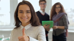 Smiling girl gestures good quality in front of man and woman with tablet Stock Footage