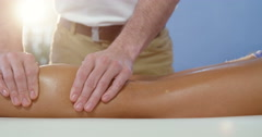 Female patient receiving leg massage from male physiotherapist Stock Footage