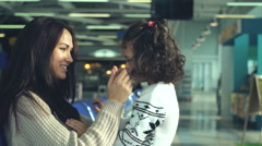 Young mother and small daughter playing in the airport terminal. Stock Footage