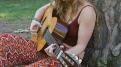 Young blonde hippie woman plays acoustic guitar outdoors. Stock Footage