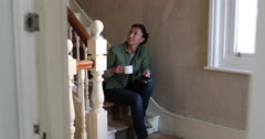 Mature female sitting on staircase in home renovation Stock Footage