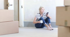 Mature female using smartphone with moving boxes Stock Footage