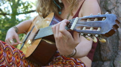 Young blonde hippie woman plays acoustic guitar outdoors. Closeup. Stock Footage