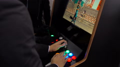 Closeup people playing video game machine. Mortal Combat 3. 4K. Man in suit play Stock Footage