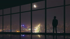 Man stand at the panoramic window on the background of night city. Time lapse Stock Footage