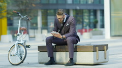 4K Stressed hipster businessman looking at tablet computer outdoors in the city Stock Footage