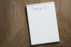 Shopping list on notepad on wood table Stock Photos