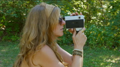Zoom in to groovy woman filming with an 8mm movie camera. Profile. Stock Footage