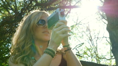 Groovy woman filming with 8mm movie camera. Sunny with lensflare. Stock Footage