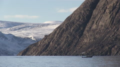 Small motor boat heads down the Arctic sea in front of snowy mountains. Stock Footage