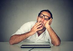 Sleepy worker man working on computer yawning Stock Photos
